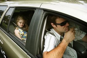 Smoking in vehicles with children is unacceptable - windows open or closed.